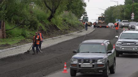 bitume : Road construction workers laying asphalt, road repairing, asphalt pavement works on city road, in consequence of which flow of cars is limited. Petropavlovsk City, Kamchatka, Russia - August 27, 2019