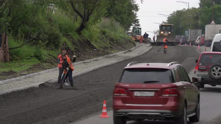 compactor : Road construction workers laying asphalt, road repairing, asphalt pavement works on city road, in consequence of which stopping traffic on road. Petropavlovsk City, Kamchatka, Russia - August 27, 2019