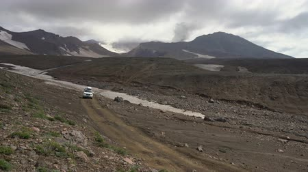 hasznosság : Japanese SUV Mitsubishi Delica driving on mountain road in direction of travel destinations for mountain adventure on active Mutnovsky Volcano. Time lapse. Kamchatka Peninsula, Russia - Aug 16, 2019 Stock mozgókép