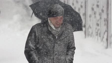 gale : Young man walking through snow on city sidewalk during snowfall, blowing snow, gale during Pacific cyclone, hiding faces from snow storm. Petropavlovsk City, Kamchatka Peninsula, Russia - Nov 15, 2019