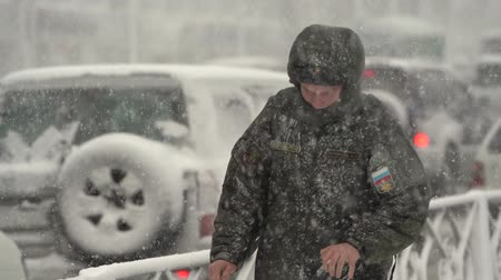 daleko : Military man in uniform walking through snow on city sidewalk during snowfall, blowing snow, gale during Pacific cyclone, hiding faces from snow storm. Petropavlovsk, Kamchatka, Russia - Nov 15, 2019