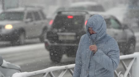 gale : Woman in blue winter jacket and hood walking through snow on city sidewalk during snowfall, blowing snow, gale during Pacific cyclone, hiding faces from snow storm. Kamchatka, Russia - Nov 15, 2019