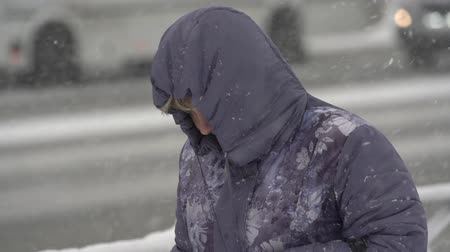 uzak : Woman in violet winter jacket, hood walking through snow on city sidewalk during snowfall, blowing snow, gale during Pacific cyclone, hiding faces from snow storm. Kamchatka, Russia - Nov 15, 2019