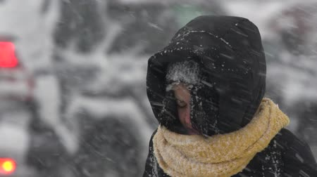 gale : Young woman in black winter jacket, yellow scarf walking sidewalk during snowfall, blowing snow, gale during Pacific cyclone, hiding faces from snow storm. Kamchatka Peninsula, Russia - Nov 15, 2019 Stock Footage