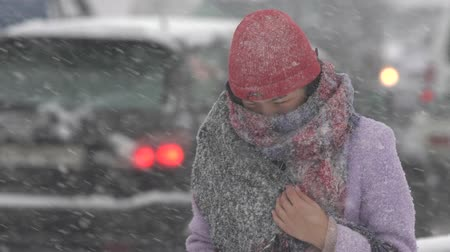 gale : Young woman in violet winter jacket walking through snow on city sidewalk during snowfall, blowing snow, gale during Pacific cyclone, hiding faces from snow storm. Kamchatka Peninsula - Nov 15, 2019