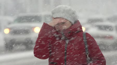 gale : Woman in red winter jacket and white beret walking through snow on sidewalk during snowfall, blowing snow, gale during Pacific cyclone, hiding faces from snow storm. Kamchatka Peninsula - Nov 15, 2019 Stock Footage