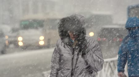 gale : Woman in shiny winter jacket and hood walking through snow on sidewalk during snowfall, blowing snow, gale during Pacific cyclone, hiding faces from snow storm. Kamchatka Peninsula - November 15, 2019 Stock Footage