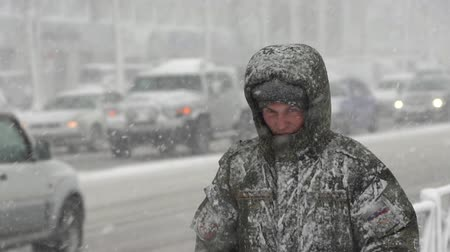 gale : Russian military man in uniform walking through snow on city sidewalk during blowing snow, snowfall, gale during Pacific cyclone, hiding faces from snow storm. Kamchatka Peninsula - November 15, 2019 Stock Footage