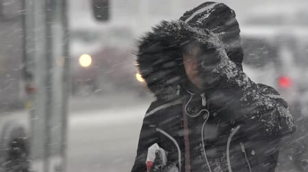 gale : Woman in black winter jacket and hood walking through snow on city sidewalk during blowing snow, snowfall, gale during Pacific cyclone, hiding faces from snow storm. Kamchatka - November 15, 2019