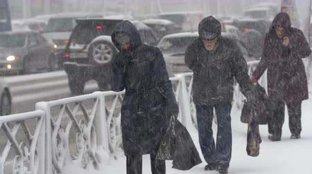 hófúvás : Group people walking through snow on sidewalk during blowing snow, snowfall, gale during Pacific cyclone, hiding faces from snow storm. Petropavlovsk City, Kamchatka Peninsula, Russia - Nov 15, 2019