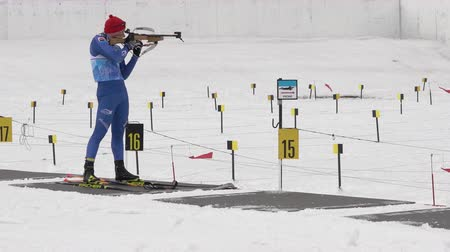 gunshot : Sportsman biathlete rifle shooting in standing position. Biathlete Leonid Bulukov in shooting range. Open regional youth biathlon competitions East Cup. Kamchatka Peninsula, Russia - April 12, 2019. Stock Footage