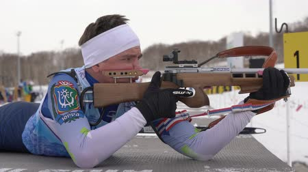 gunshot : Sportsman biathlete rifle shooting in prone position. Biathlete Andrey Krutov in shooting range. Open regional youth biathlon competitions East Cup. Kamchatka Peninsula, Russia - April 12, 2019. Stock Footage
