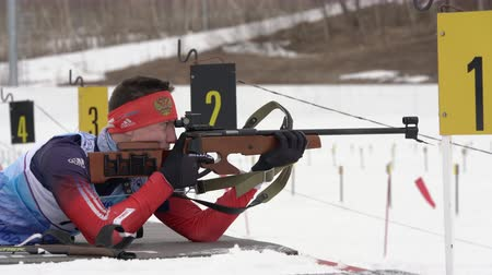 aim : Sportsman biathlete rifle shooting in prone position. Biathlete Kapustin Aleksander in shooting range. Open regional youth biathlon competitions East Cup. Kamchatka Peninsula, Russia - April 12, 2019.