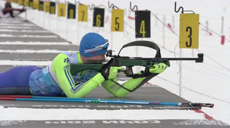 posição : Sportsman biathlete rifle shooting in prone position. Biathlete Napersnikov Nikita in shooting range. Open regional youth biathlon competitions East Cup. Kamchatka Peninsula, Russia - April 12, 2019.