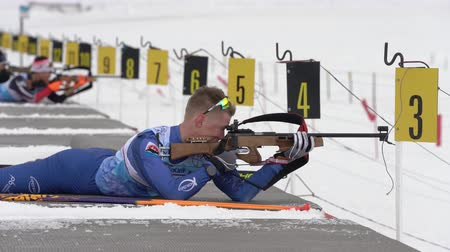 biathlete : Sportsman biathlete rifle shooting in prone position. Biathlete Kozulin Aleksander in shooting range. Open regional youth biathlon competitions East Cup. Kamchatka Peninsula, Russia - April 12, 2019.