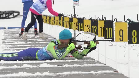 gunshot : Sportsman biathlete rifle shooting in prone position. Biathlete Butkhuyag Taivanbaatar Mongolia in shooting range. Regional youth biathlon competitions East Cup. Kamchatka, Russia - April 12, 2019