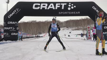 biathlete : Kamchatka sportsman biathlete Konovalov Vyacheslav skiing at finish line after sprint and rifle shooting. Open regional youth biathlon competitions East Cup. Kamchatka Peninsula, Russia - Apr 12, 2019