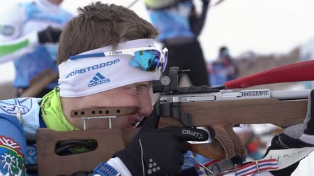 prone position : Sportsman biathlete aiming, rifle shooting and reloading rifle in prone position. Biathlete Morilov Mikhail in shooting range. Youth biathlon competitions East Cup. Kamchatka, Russia - April 12, 2019.