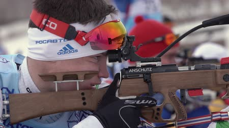reloading : Sportsman biathlete aiming, rifle shooting and reloading rifle in prone position. Biathlete Zlobin Vladislav in shooting range. Youth biathlon competitions East Cup. Kamchatka, Russia - April 12, 2019 Stock Footage