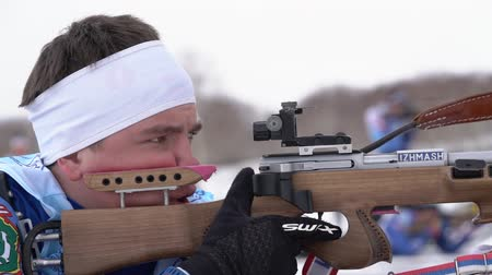 prone position : Sportsman biathlete aiming, rifle shooting and reloading rifle in prone position. Biathlete Andrey Krutov in shooting range. Youth biathlon competitions East Cup. Kamchatka, Russia - April 12, 2019.