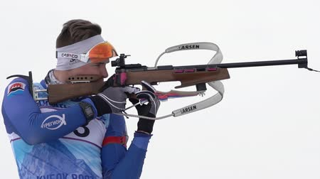 biathlete : Sportsman biathlete aiming and rifle shooting, reloading rifle in standing position. Biathlete Ageev Danil in shooting range. Youth biathlon competitions East Cup. Kamchatka, Russia - April 12, 2019.