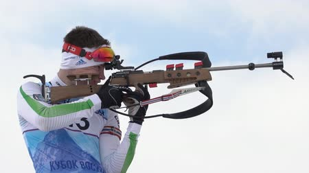 reloading : Sportsman biathlete aiming, rifle shooting, reloading rifle in standing position. Biathlete Zlobin Vladislav in shooting range. Youth biathlon competitions East Cup. Kamchatka, Russia - April 12, 2019 Stock Footage