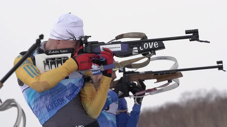 biathlete : Group sportsmans biathlete aiming and rifle shooting, reloading rifle in standing position. Biathletes in shooting range. Youth biathlon competitions East Cup. Kamchatka, Russia - April 12, 2019 Stock Footage