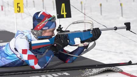 biathlete : Sportswoman biathlete aiming, rifle shooting in prone position. Biathlete Starovoitova Anna Saint Petersburg in shooting range. Junior biathlon competitions East Cup. Kamchatka, Russia - Apr 13, 2019