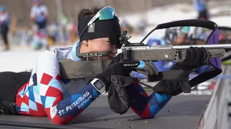 biathlete : Sportswoman biathlete aiming, rifle shooting in prone position. Biathlete Shishkina Vlada Saint Petersburg in shooting range. Junior biathlon competitions East Cup. Kamchatka, Russia - April 13, 2019. Stock Footage