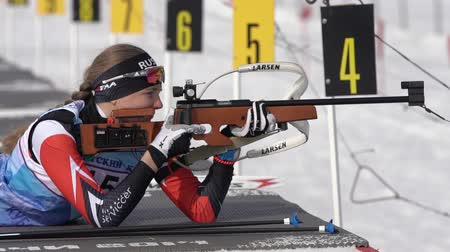 gunshot : Sportswoman biathlete aiming, rifle shooting and reloading in prone position. Biathlete Eremeeva Elizaveta in shooting range. Junior biathlon competitions East Cup. Kamchatka, Russia - April 13, 2019