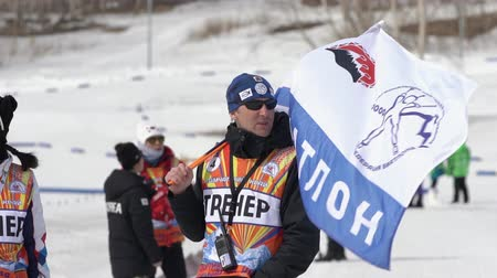 biathlete : Biathlon team coach waving sports flag with emblem Kamchatsky Krai, logo Kamchatka Biathlon Federation. Junior biathlon competitions East of Cup. Petropavlovsk City, Kamchatka, Russia - April 13, 2019