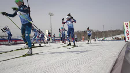 mass start : Mass start Regional junior biathlon competitions East of Cup - group of sportswoman biathlete skiing on biathlon stadium. Petropavlovsk City, Kamchatka Peninsula, Russian Far East - April 13, 2019 Stock Footage