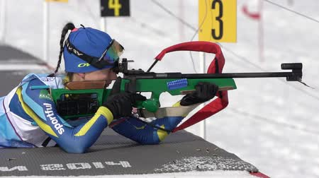 kazahsztán : Sportswoman biathlete aiming, rifle shooting, reloading prone position. Biathlete Arina Kryukova Kazakhstan in shooting range. Junior biathlon competitions East Cup. Kamchatka, Russia - Apr 13, 2019 Stock mozgókép