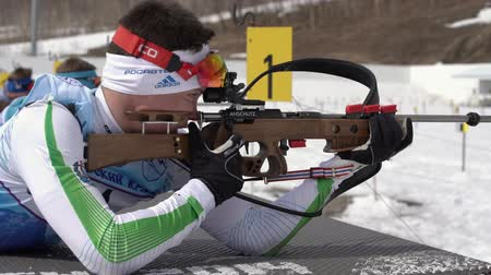prone position : Sportsman biathlete aiming, rifle shooting in prone position. Khanty-Mansiysk biathlete Zlobin Vladislav in shooting range. Junior biathlon competitions East Cup. Kamchatka, Russia - April 13, 2019 Stock Footage