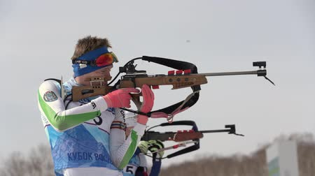 biathlete : Sportsman biathlete aiming, rifle shooting in standing position. Khanty-Mansiysk biathlete Rusinov Vladislav in shooting range. Junior biathlon competitions East Cup. Kamchatka, Russia - Apr 13, 2019