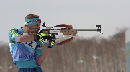 ジュニア : Sportsman biathlete aiming, rifle shooting in standing position. Kazakhstan biathlete Vladislav Kireyev in shooting range. Junior biathlon competitions East Cup. Kamchatka, Russia - April 13, 2019 動画素材