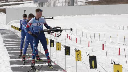 biathlete : Group of sportsman biathlete aiming, rifle shooting in standing position on shooting range biathlon arena. Junior biathlon competitions East Cup. Kamchatka Peninsula, Russian Far East - April 13, 2019