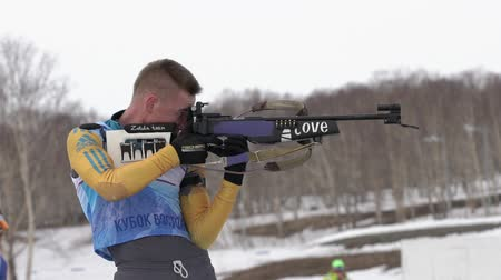 shooting range : Sportsman biathlete aiming, rifle shooting, reloading standing position. Kazakhstan biathlete Kurales Vadim in shooting range. Junior biathlon competitions East Cup. Kamchatka, Russia - April 13, 2019