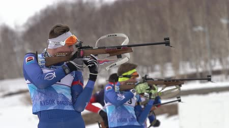 gunshot : Sportsman biathlete aiming, rifle shooting, reloading in standing position. Kamchatka biathlete Ageev Danil in shooting range. Junior biathlon competitions East Cup. Kamchatka, Russia - April 13, 2019