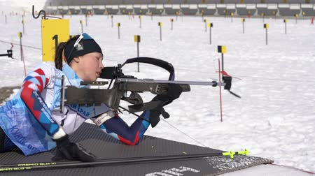 posição : Sportswoman biathlete aiming, rifle shooting prone position. Biathlete Pashitova Karina Saint Petersburg in shooting range. Junior biathlon competitions East of Cup. Kamchatka, Russia - April 13, 2019