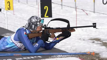 reloading : Sportswoman biathlete aiming, rifle shooting prone position. Biathlete Arina Soldatova in shooting range. Regional junior biathlon competitions East Cup. Kamchatka Peninsula, Russia - April 13, 2019.