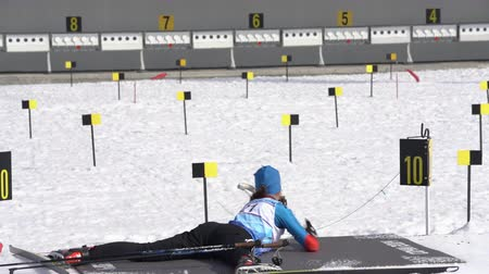 biathlon : Sportswoman biathlete aiming, rifle shooting prone position. Kamchatka biathlete Soenko Violetta in shooting range. Junior biathlon competitions East of Cup. Kamchatka Peninsula, Russia - Apr 13, 2019 Stock Footage