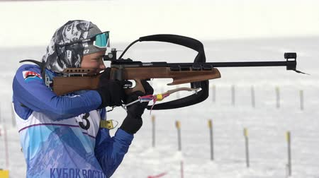 reloading : Sportswoman biathlete aiming, rifle shooting standing position. Biathlete Arina Soldatova in shooting range. Regional junior biathlon competitions East Cup. Kamchatka Peninsula, Russia - Apr 13, 2019.
