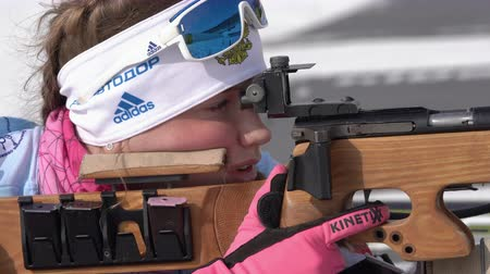reloading : Sportswoman biathlete aiming, rifle shooting standing position. Biathlete Shishkina Vlada Saint Petersburg in shooting range. Junior biathlon competitions East Cup. Kamchatka, Russia - April 13, 2019. Stock Footage