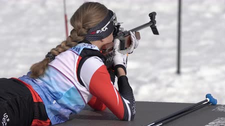 posição : Sportswoman biathlete aiming, rifle shooting prone position. Kamchatka biathlete Eremeeva Elizaveta in shooting range. Junior biathlon competitions East Cup. Kamchatka Peninsula, Russia - Apr 13, 2019