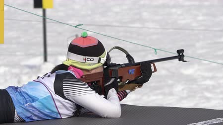 prone position : Sportswoman biathlete aiming, rifle shooting prone position. Biathlete Choi Yoonah South Korea in shooting range. Junior biathlon competitions East of Cup. Kamchatka Peninsula, Russia - April 13, 2019