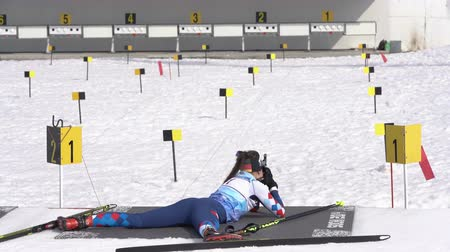 prone position : Sportswoman biathlete aiming, rifle shooting prone position. Saint Petersburg biathlete Karina Pashitova in shooting range. Junior biathlon competitions East of Cup. Kamchatka, Russia - April 13, 2019 Stock Footage