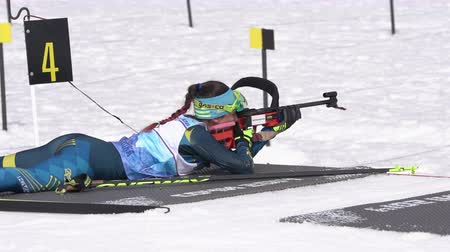 gunshot : Sportswoman biathlete aiming rifle shooting standing position. Biathlete Polina Yegorova Kazakhstan in shooting range. Junior biathlon competitions East Cup. Kamchatka Peninsula, Russia - Apr 13, 2019