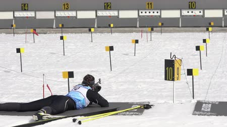 russian far east : Sportswoman biathlete aiming, rifle shooting, reloading in prone position. Biathlete Knyazeva Elizaveta in shooting range. Junior biathlon competitions East of Cup. Kamchatka, Russia - April 13, 2019.
