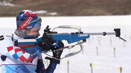 gunshot : Sportswoman biathlete aiming, rifle shooting and reloading standing position. Biathlete Anna Starovoitova in shooting range. Junior biathlon competitions East Cup. Kamchatka, Russia - April 13, 2019. Stock Footage